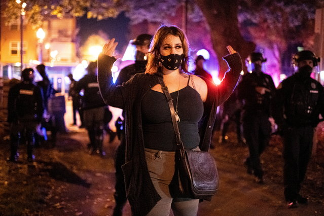 A protester holds up her hands as police detain other protesters and clear a park after a vigil and march marking the shooting death by police of Black man Kevin E. Peterson Jr. in Vancouver, Washington, U.S. October 31, 2020. (Photo by Mathieu Lewis-Rolland/Reuters)
