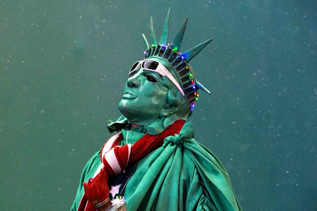 A street performer dressed as the Statue of Liberty stands amongst light snow in Times Square in New York December 10, 2014. Snow showers fell in the region through Wednesday and should clear early Thursday. (Photo by Andrew Kelly/Reuters)