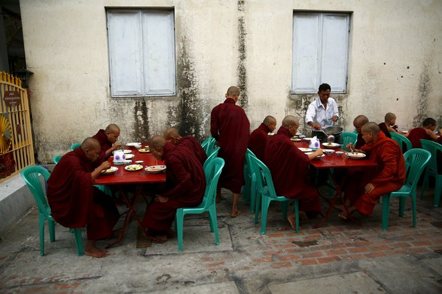 Buddhist monks eat breakfast outside a monastery in Mandalay October 7, 2015. (Photo by Jorge Silva/Reuters)