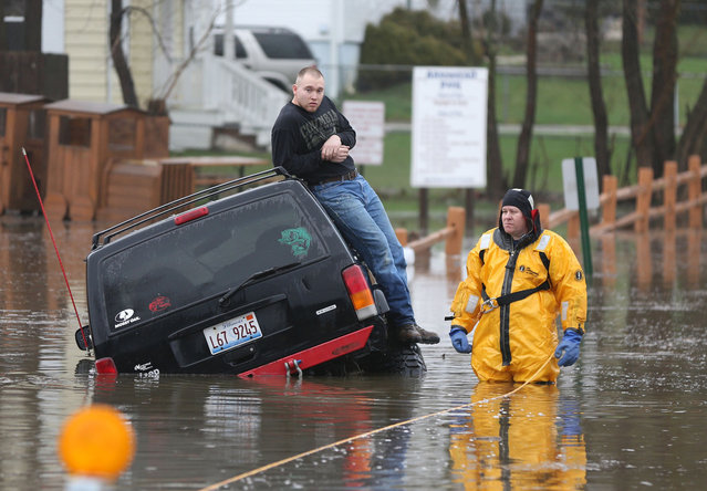 A rescue official stands with a motorist stuck in water during heavy rains and flooding in Round Lake Heights, Illinois, Thursday, April 18, 2013, at Pontiac Court and Tomahawk Trail. (Photo by Joe Shuman/Chicago Tribune/MCT)