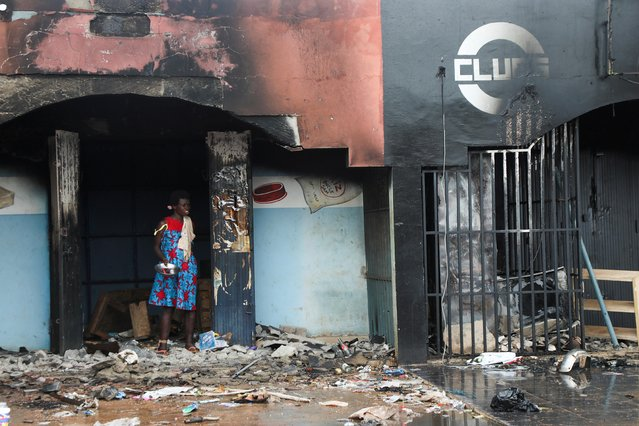 A woman stands near the rubble of a burnt store after post electoral inter-community clashes on Monday and Tuesday, in M'Batto, Ivory Coast on November 12, 2020. (Photo by Luc Gnago/Reuters)