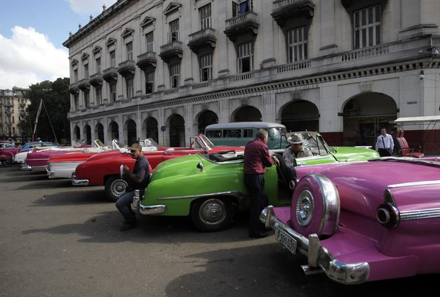 Drivers stand near their vintage cars waiting for clients in Havana December 17, 2014. (Photo by Reuters/Stringer)