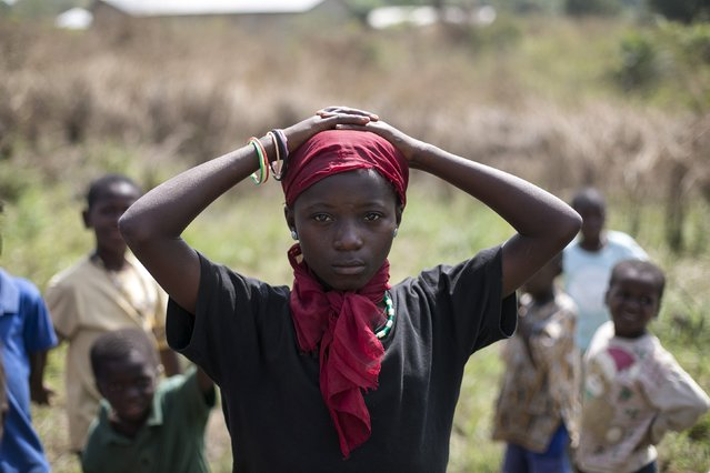 A girl waits for a helicopter to take off in the town of Koidu, Kono district in Eastern Sierra Leone, December 18, 2014. Sierra Leone, neighbouring Guinea and Liberia are at the heart of the world's worst recorded outbreak of Ebola. Rates of infection are rising fastest in Sierra Leone, which now accounts for more than half of the 18,603 confirmed cases of the virus. (Photo by Baz Ratner/Reuters)