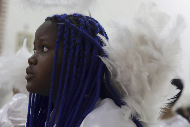 In this October 7, 2016 photo, a girl dressed as an angel attends a Mass in honor of Our Lady of Rosario during the annual Afro-Christian Congada celebration in Catalao, Goias state, Brazil. Some children participate in the annual celebration dressed as angels, considered a sacred symbol representing purity. (Photo by Eraldo Peres/AP Photo)