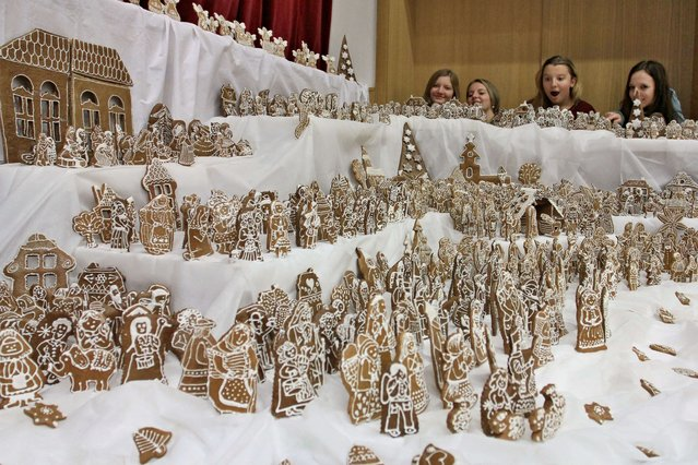 Visitors look at a nativity scene made of gingerbread on November 30, 2014 in Zdounky, central Moravia, Czech Republic. About ten women worked more than a month on the nativity scene, using 45 kilograms of dough and 120 eggs to manufacture a total of 1,806 gingerbread pieces. (Photo by Radek Mica/AFP Photo)