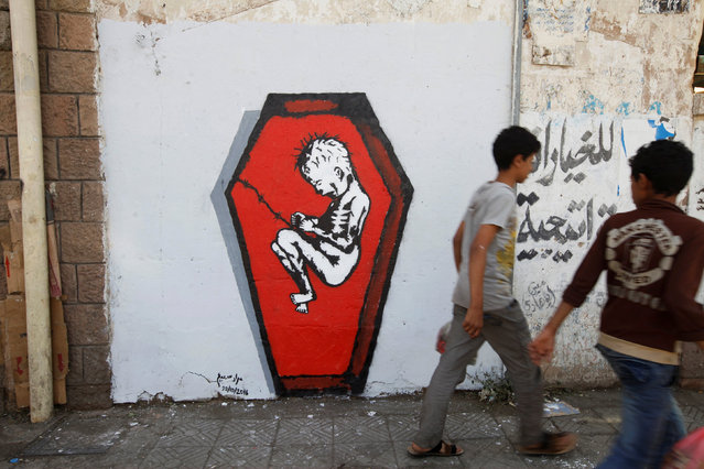 """Boys walks pass a graffiti of artist Murad Subai depicting a child suffering from malnutrition in a coffin along a street in Sanaa, Yemen, October 20, 2016. The graffiti is part of a campaign by several artists titled """"Ruins"""" which focuses on the issue of malnutrition, hunger and disease because of war. (Photo by Mohamed al-Sayaghi/Reuters)"""