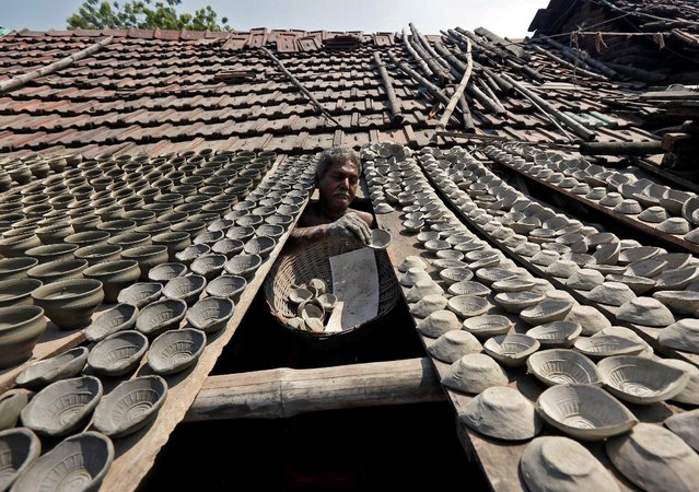 A potter dries earthen lamps, which are used to decorate temples and homes during Diwali, the Hindu festival of lights, on a wooden slab attached to a rooftop at a workshop in Kolkata, India October 19, 2016. (Photo by Rupak De Chowdhuri/Reuters)