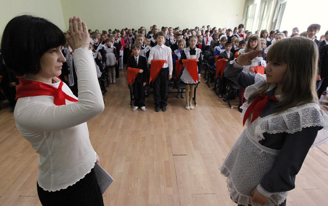 Children, wearing red neckerchiefs, a symbol of the Young Pioneer Organisation, stand in the background while the chairman of a pioneer team (R) salutes a school teacher and the local pioneer leader during a ceremony for the inauguration of 55 newly adopted members on the day of its anniversary at school-lyceum number 12 in Russia's Siberian city of Krasnoyarsk May 19, 2011. (Photo by Ilya Naymushin/Reuters)