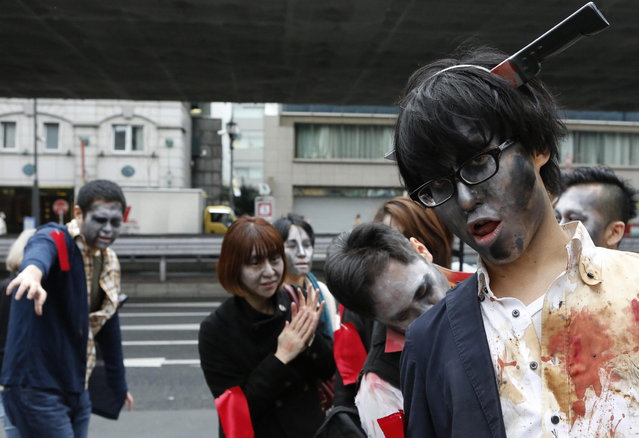 People, dressed as zombies, participate in the Roppongi Zombie Walk in Tokyo March 31, 2013. About 50 people dressed up as zombies early evening on Sunday, catching the attention of pedestrians on the streets of Tokyo's downtown Roppongi district. (Photo by Yuya Shino/Reuters)