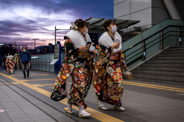 "Twenty-year-old women dressed in kimonos walk during sunset after the ""Coming-of-Age Day"" celebration Yokohama Arena in Yokohama on January 11, 2021 under a state of emergency over the Covid-19 coronavirus pandemic. (Photo by Philip Fong/AFP Photo)"