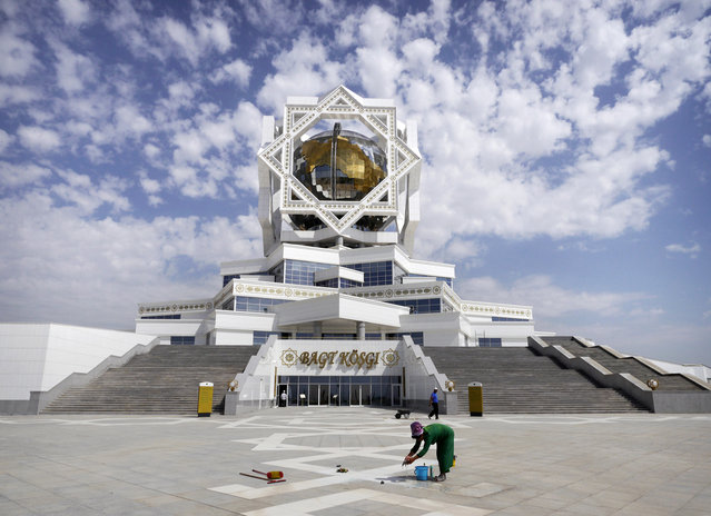 """A cleaner at work in front of Ashgabat's """"Palace of Happiness"""". The wedding venue features a room where newlyweds are required to pose in front of a portrait of the President. Radio Free Europe subsequently dubbed Berdimuhamedow """"Photobomber-in-Chief"""". (Photo by Amos Chapple via The Atlantic)"""