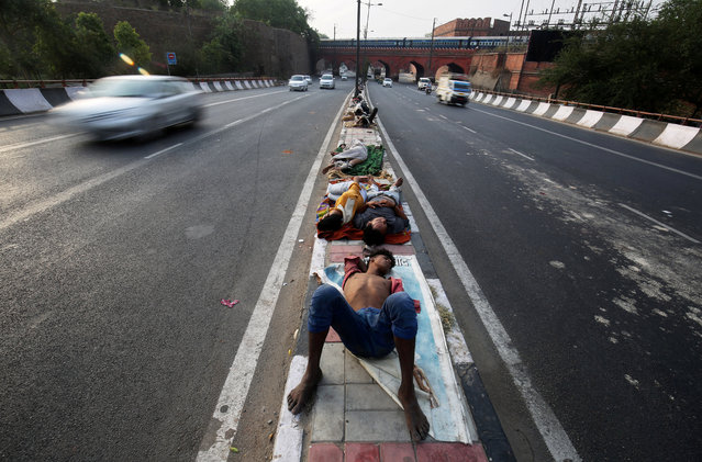 People sleep on a road divider in New Delhi, India, June 1, 2018. (Photo by Amit Dave/Reuters)