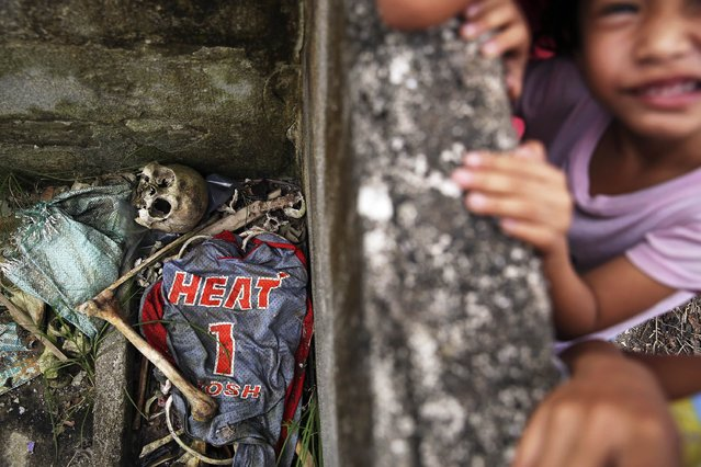 Children play in ruins above human remains and a basketball shirt found with it in the coastal part of Tacloban, that was destroyed by Typhoon Haiyan, January 16, 2015. (Photo by Damir Sagolj/Reuters)