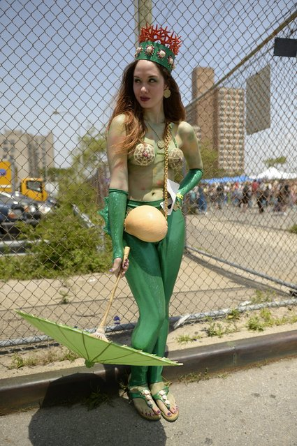 A parade participant arrives in costume for the 31st Annual Mermaid Parade at New York's Coney Island on June 22, 2103. Over 700,00 people are exptected to turn out for the  scantily clad parade.       AFP PHOTO / TIMOTHY CLARY        (Photo credit should read TIMOTHY CLARY/AFP/Getty Images)