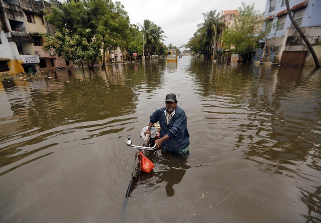 A man wades through a flooded road along with his bicycle in Chennai, India, December 5, 2015. (Photo by Anindito Mukherjee/Reuters)