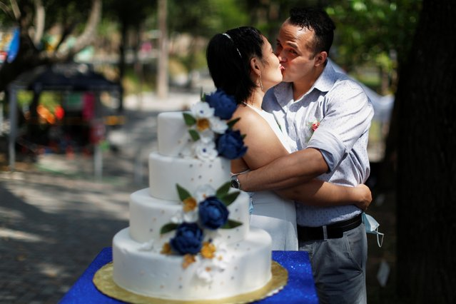 A newly-wed couple kisses after a collective wedding ceremony celebrated by the municipality, as the coronavirus disease (COVID-19) outbreak continues on Valentine's Day, in San Salvador, El Salvador on February 14, 2021. (Photo by Jose Cabezas/Reuters)