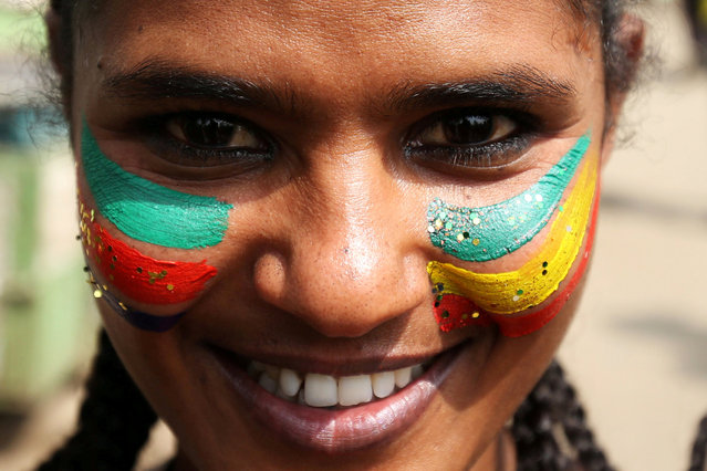 A woman with a face painting of the Ethiopia national flag attends a ceremony to welcome Eritrea's President Isaias Afwerki for a three-day visit, at the Bole international airport in Addis Ababa, Ethiopia July 14, 2018. (Photo by Tiksa Negeri/Reuters)