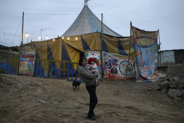 In this July 8, 2018 photo, a woman with her baby waits for one of her daughters to arrive before entering the Tony Perejil circus tent, set up in the shantytown of Puente Piedra on the outskirts of Lima, Peru. Tickets cost 6 Soles (2 dollars) for adults, and are half price for children. (Photo by Martin Mejia/AP Photo)