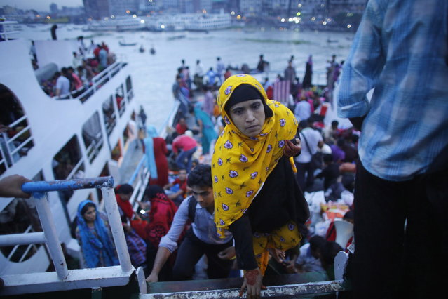 A woman boards on an overcrowded passenger boat at Sadarghat boat terminal in Dhaka August 7, 2013. Millions of residents in Dhaka have started the exodus home from the capital city ahead of the Eid al-Fitr holiday, which marks the end of the fasting month of Ramadan. (Photo by Andrew Biraj/Reuters)