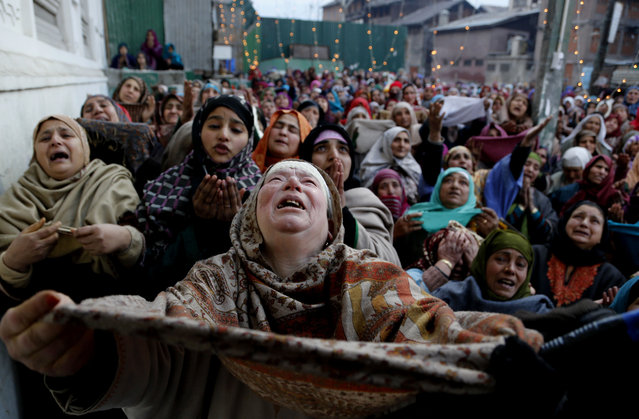 Kashmiri Muslim devotees pray as the head priest displays a relic of Sufi Saint Syed Abdul Qadir Jilani outside his shrine in Srinagar, India, Sunday, February 1, 2015. Thousands of devotees thronged the shrine Sunday to mark the saint's Urs or yearly commemoration. (Photo by Mukhtar Khan/AP Photo)