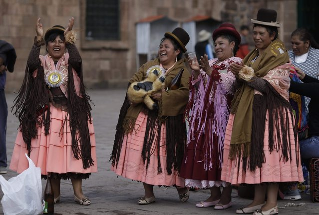 """In this Sunday, August 5, 2018 photo, Andean dancers known as """"cholas"""" applaud the fancy footwork of a couple, as they take a break from their performance honoring Our Lady of Copacabana, in Cuzco, Peru. """"Cholas"""", who make up part of the traditional Bolivian dance known as the """"Morenada"""" or Dance of the Black Slaves, are easily identifiable by their typical Aymara dress: wide skirts, bowler hats and elaborate shawls. (Photo by Martin Mejia/AP Photo)"""