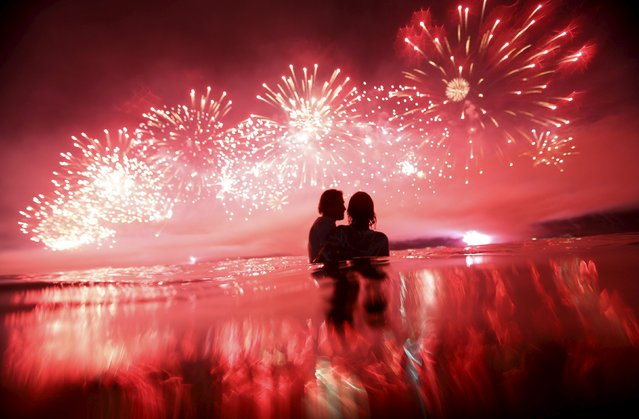 A couple watch as fireworks explode over Copacabana beach during New Year celebrations in Rio de Janeiro, Brazil, January 1, 2016. (Photo by Ricardo Moraes/Reuters)