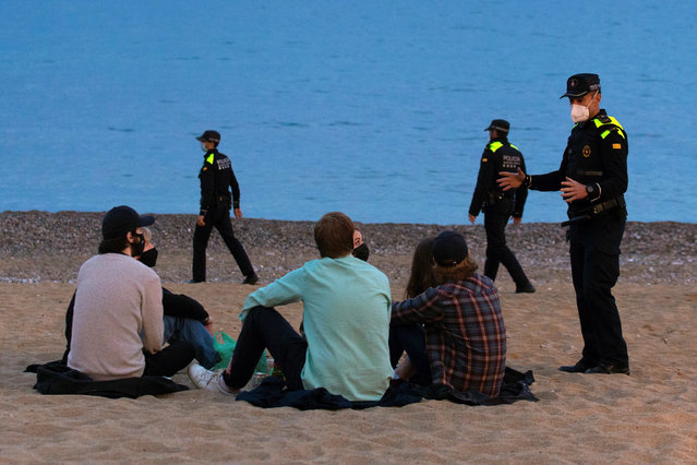 Police officers disperse a group of youths who gathered to have drinks on the beach by disobeying the security measures due to the pandemic, in Barcelona, Spain, 03 April 2021. Police dispersed more than 500 people on 03 April for the same reason in different locations of the city. (Photo by Enric Fontcuberta/EPA/EFE)