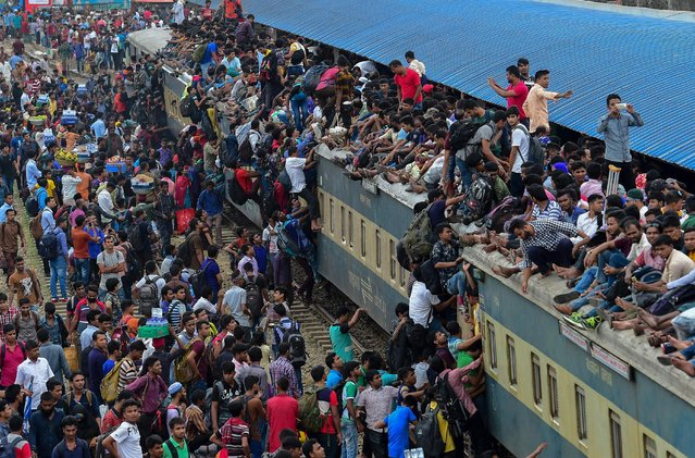 People scramble to reach the roof of an overcrowded train at a station in Dhaka on August 20, 2018. Muslims across the world celebrate the annual festival of Eid al- Adha, or the Festival of Sacrifice, which marks the end of the Hajj pilgrimage to Mecca and in commemoration of Prophet Abraham' s readiness to sacrifice his son to show obedience to God. (Photo by Munir Uz Zaman/AFP Photo)