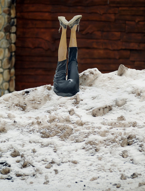 The lower half of a mannequin is stuck in a deep pile of snow and ice in front of a home, Tuesday, February 10, 2015, in Covington Township, Pa. (Photo by Butch Comegys/AP Photo/The Times & Tribune)
