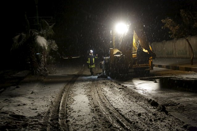 A civil defense member guides a snowplough opening a road in the rebel-controlled area of Maaret al-Numan town in Idlib province, Syria January 4, 2016. (Photo by Khalil Ashawi/Reuters)