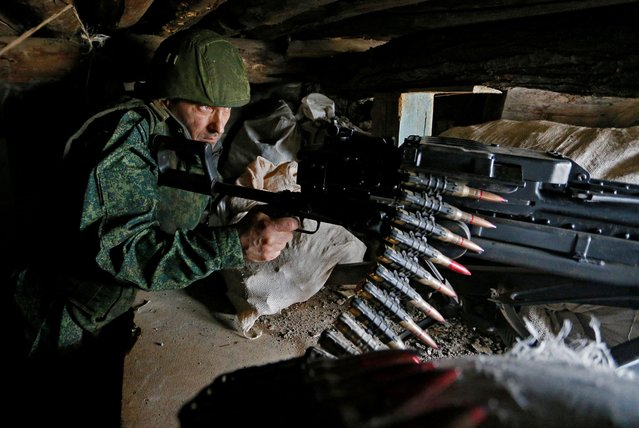 A militant of the self-proclaimed Luhansk People's Republic (LNR) points a weapon at fighting positions on the line of separation from the Ukrainian armed forces in Luhansk Region, Ukraine on April 13, 2021. (Photo by Alexander Ermochenko/Reuters)