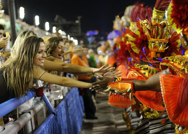 Parade goers greet Beija Flor samba school performers as they file past during Carnival celebrations at the Sambadrome in Rio de Janeiro, Brazil, Tuesday, February 17, 2015. (Photo by Silvia Izquierdo/AP Photo)