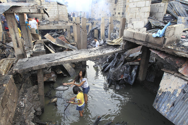 Residents search for reusable items after a fire hit a residential area at Merville park in Pasay city, metro Manila February 16, 2015. At least four people were killed after a fire razed an estimated 300 houses made of light materials, local media reported. (Photo by Romeo Ranoco/Reuters)
