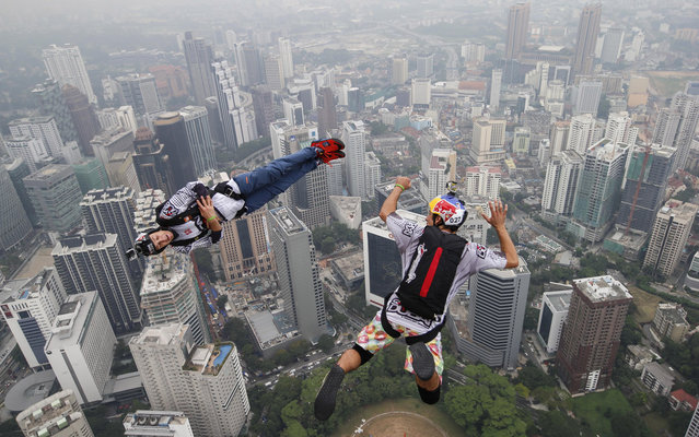 Base jumper Jean-Philippe Marie Teffaud, left, and his team mate Frederic Yves Fugen of France leap from the 300-meter Open Deck of the Malaysia's landmark Kuala Lumpur Tower during the International Tower Jump in Kuala Lumpur, Friday, September 27, 2013. About 103 professional base jumpers from 20 countries took part in the annual event. (Photo by Vincent Thian/AP Photo)