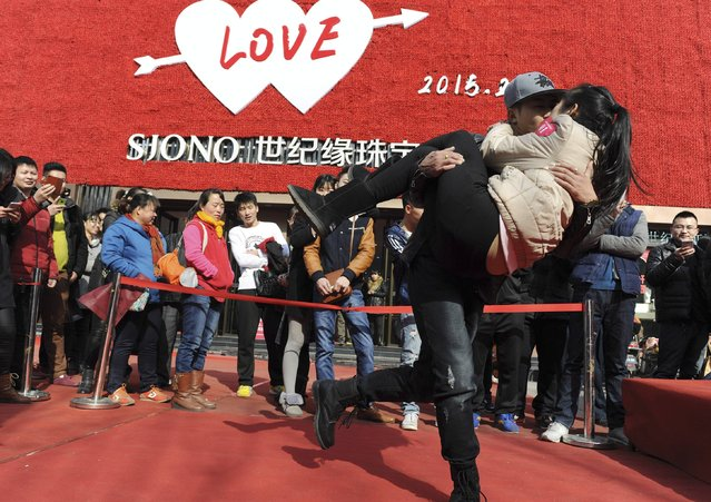 A couple kisses during a kissing contest on Valentine's Day in Jinan, Shandong province, February 14, 2015. Some 40 couples attended the contest and the winners were awarded a diamond ring and a monetary reward of 214 yuan ($34), according to local media. (Photo by Reuters/Stringer)