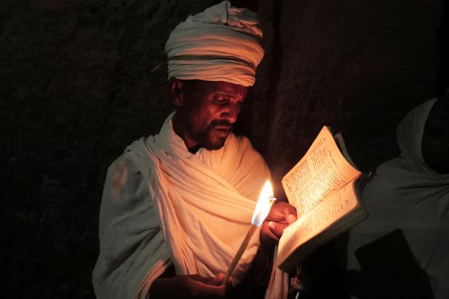 An Ethiopian Orthodox Priest reads a Bible during the Easter Eve celebration at the St. Mary Rock-Hewn church in Lalibela, Ethiopia, May 1, 2021. (Photo by Tiksa Negeri/Reuters)