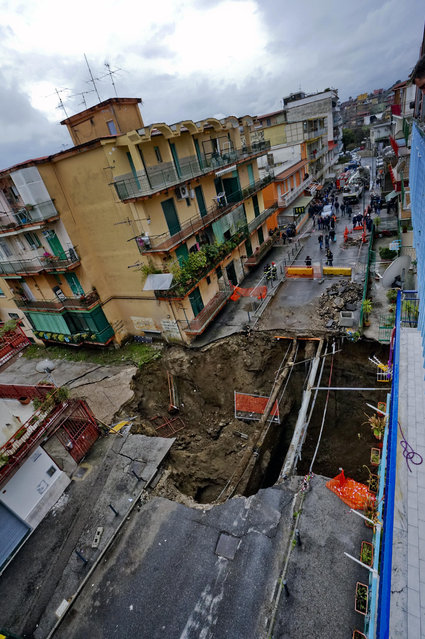 In this photo taken Sunday, February 22, 2015 and made available Monday, February 23 view from above of the chasm that opened Saturday and enlarged in the night, forcing the evacuation of about 380 people, in the Pianura district of Naples, Italy. (Photo by Ciro Fusco/AP Photo/Ansa)