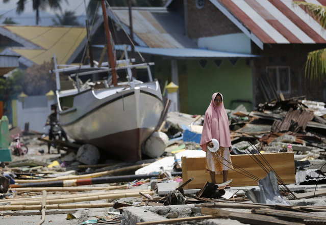 A woman stands in the rubble of houses as a boat swept ashore by tsunami rests on the ground in the background in Wani village on the outskirt of Palu, Central Sulawesi, Indonesia, Wednesday, October 10, 2018. A 7.5 magnitude earthquake rocked Central Sulawesi province on Sept. 28, triggering a tsunami and mudslides that killed a large number of people and displaced tens of thousands of others. (Photo by Dita Alangkara/AP Photo)