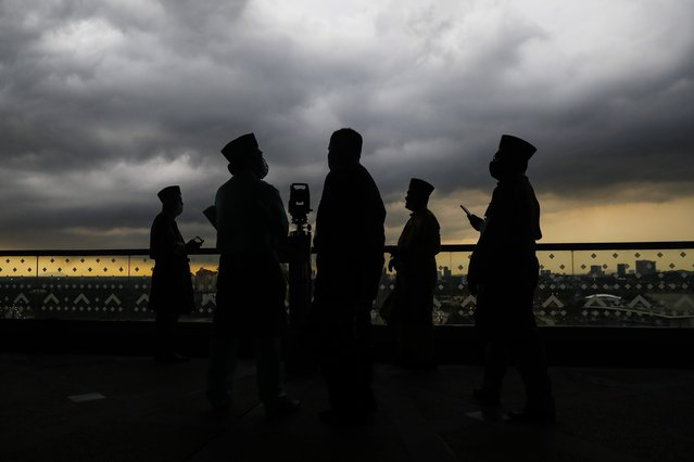 A silhouette of Malaysian Islamic religious officers as they observe the position of the moon using a theodolite to determine the sighting of the new moon to mark the start of the fasting month of Ramadan in Putrajaya, Malaysia, 12 April 2021. During Ramadan, the ninth month of Islam's lunar calendar, observant Muslims abstain from eating, drinking and smoking from dawn to dusk. Fasting is one of Islam's five pillars, alongside declaration of faith, prayer five times a day, alms-giving, and the pilgrimage to holy sites in Saudi Arabia. (Photo by Fazry Ismail/EPA/EFE)