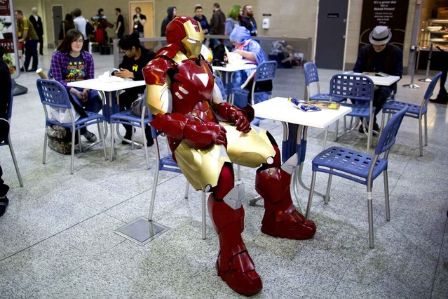 A man dressed as Ironman takes a seat in the cafeteria on the second day of the London Super Comic Convention at the ExCel centre in east London, on March 15, 2015. (Photo by Justin Tallis/AFP Photo)