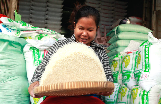 A Cambodian woman prepares rice for sale at a market in Phnom Penh, Cambodia, 28 January 2016. According to local media report Cambodian private rice exporting companies exported 538,396 tons of milled rice in 2015 as their goal to export one million tons of milled rice per year. (Photo by Tep Sony/EPA)