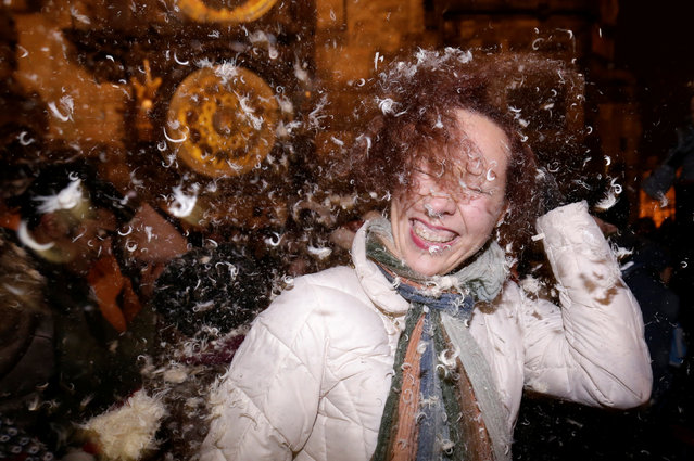 A woman takes part in a four-minute flash mob pillow fight at the Old Town Square in Prague, Czech Republic, December 22, 2016. (Photo by David W. Cerny/Reuters)