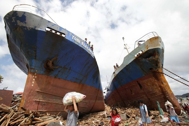 Survivors pass by two large boats after they were washed ashore by strong waves caused by Typhoon Haiyan in Tacloban city, Leyte province central Philippines on Sunday, November 10, 2013. Typhoon Haiyan, one of the strongest storms on record, slammed into six central Philippine islands on Friday leaving a wide swath of destruction and hundreds of people dead. (Photo by Aaron Favila/AP Photo)