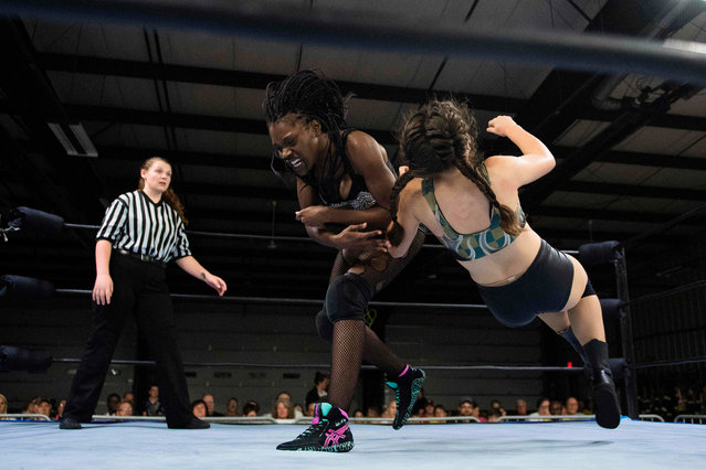 Professional wrestler Gia Scott (C) baby checks professional wrestler Aria Palmer (R) during Autumn Armageddon 2018 in Galena, Maryland on October 6, 2018. (Photo by Jim Watson/AFP Photo)