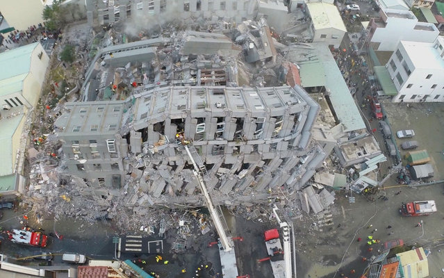 In this photo taken from a drone mounted camera, rescue workers search a collapsed building from an early morning earthquake in Tainan, Taiwan, Saturday, February 6, 2016. A powerful, shallow earthquake struck southern Taiwan before dawn Saturday. (Photo by AP Photo)