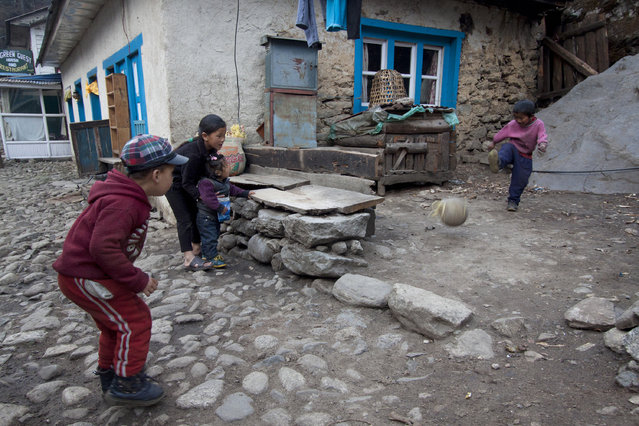 In this Tuesday, March 24, 2015 photo, children play football in Phakding, one of the main resting point for Everest trekkers, Nepal. (Photo by Tashi Sherpa/AP Photo)