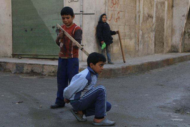 Children play with toy weapons along a street in the al-Jazmati neighbourhood of Aleppo February 1, 2015. (Photo by Hosam Katan/Reuters)