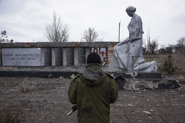 """A pro-Russian rebel stands in froth of a WWII monument with words reading """"Your feat is immortal, eternal glory to you!"""" near their position at the frontline in a  village not far from Luhasnk, eastern Ukraine, Thursday, March 12, 2015. (Photo by Mstyslav Chernov/AP Photo)"""