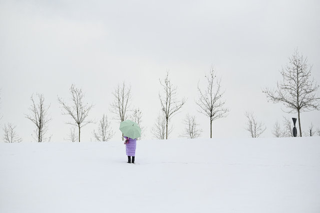 A pedestrian carrying an umbrella walks on a snowy road, near Pristina, Kosovo on March 24, 2021 following a week of heavy snowfall. (Photo by Armend Nimani/AFP Photo)