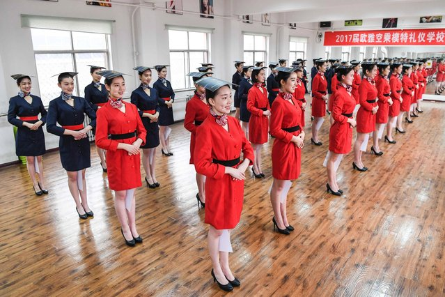 Students attend a stewardess skill training for the upcoming 2017 entrance examination for art majors in colleges in Luoyang, central China's Henan Province, January 4, 2017. These photos portray the bizarre range of skills Chinese air hostesses require before they take to the skies. (Photo by Li Bo/Xinhua/Barcroft Images)